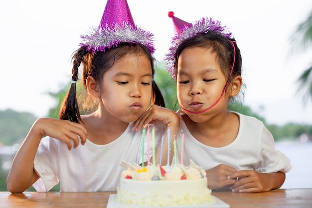 Twee aziatische kindmeisjes die verjaardag vieren en kaarsen op verjaardagscake in de partij blazen