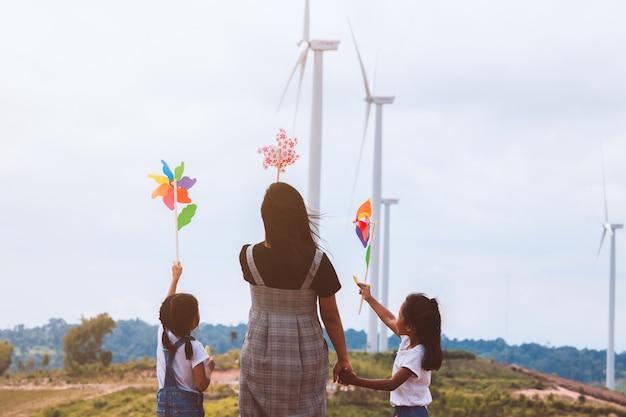 Twee aziatische kindmeisjes en hun moeder die met het stuk speelgoed van de windturbine samen met pret spelen