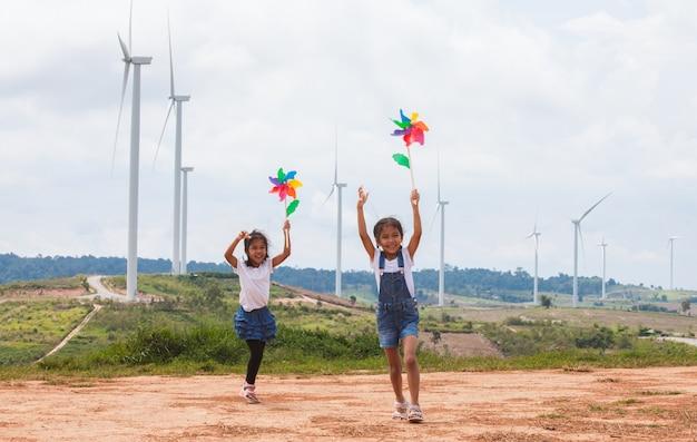 Twee aziatische kindmeisjes lopen samen en spelen met het stuk speelgoed van de windturbine