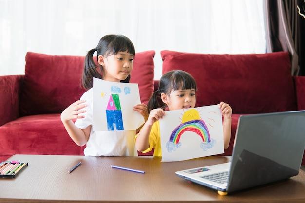 Twee aziatische kindmeisjesstudenten studeren samen online met de leraar door middel van een videogesprek.