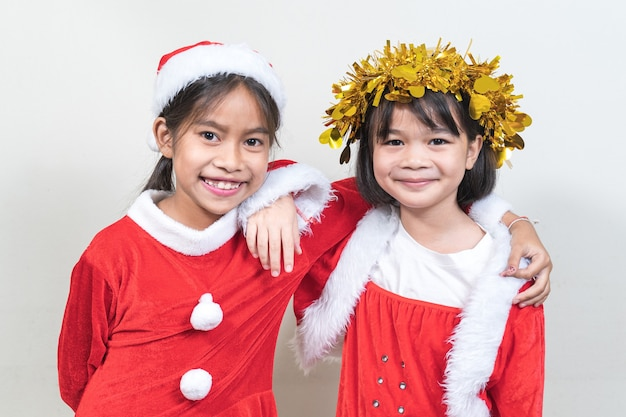 Twee aziatische kleine kindermeisjes die een rood kerstmanpak dragen om kerstvakantie thuis te vieren