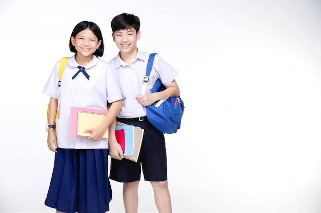 Twee aziatische lachende schoolkinderen met kleurrijke briefpapier,