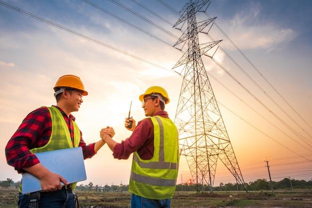 Twee aziatische mannen met elektrotechnisch ingenieurs die zich bij de krachtcentrale bevinden die in de lucht handen schudden die akkoord gaan met de productie van stroom.
