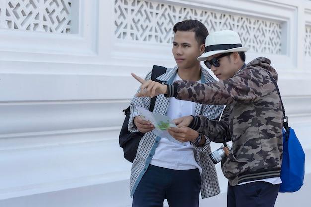 Twee aziatische mannenreizigers die kaart zoeken bij een tempel rachaburana, wat zijn de attractieslocatie op de kaart.