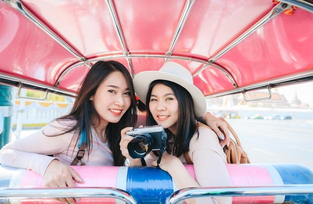 Twee aziatische meisjes beste vriendenreiziger zitten in tuk tuk-taxi