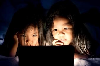 Twee aziatische meisjes die digitale tablet gebruiken bij nacht in de slaapkamer in donkerblauwe kleurentoon