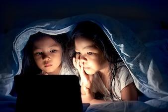 Twee aziatische meisjes die digitale tablet gebruiken onder deken bij nacht in donkerblauwe kleurentoon