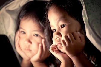 Twee aziatische meisjes die digitale tablet gebruiken onder deken bij nacht in uitstekende kleurentoon