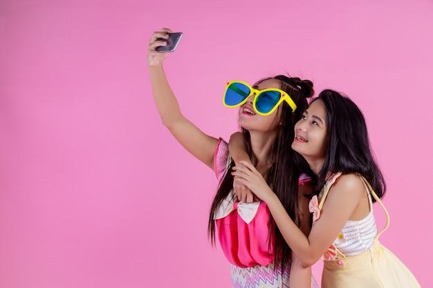 Twee aziatische meisjes die vrienden zijn, zijn gelukkig en hebben een roze.
