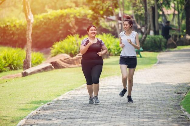Twee aziatische meisjes dikke en dunne vriend lopende jogging in het park