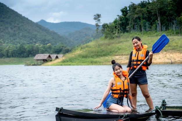 Twee aziatische meisjes in oranje reddingsvesten de ene persoon houdt een peddel, de andere zit, tegen de achtergrond van water en bergen. klaar om te reizen als hobby.