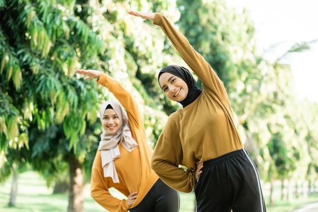 Twee aziatische meisjes in sluier strekken zich uit door hun armen omhoog te heffen met hun lichaam opzij leunend voordat ze in het park gaan trainen