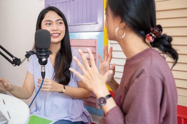 Twee aziatische meisjes met handgebaar tijdens het chatten met microfoon op podcast