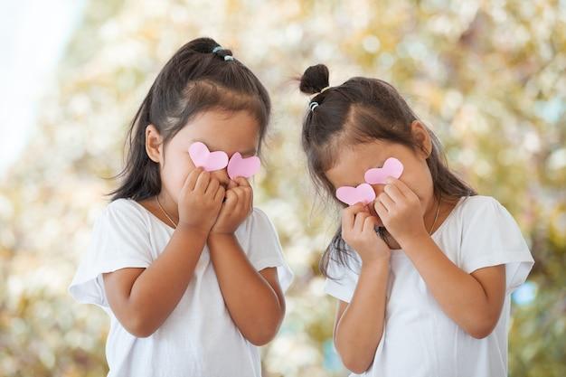 Twee aziatische meisjes met harten op hun ogen
