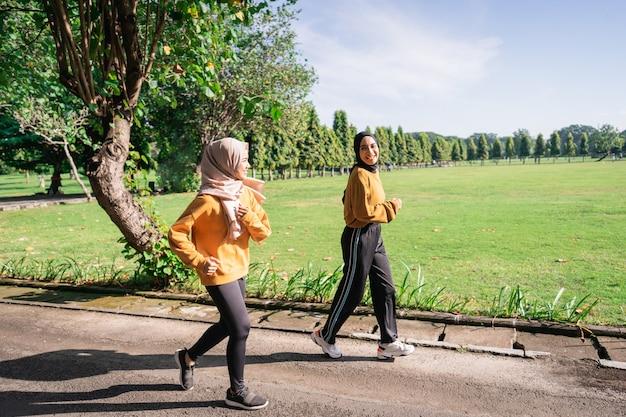 Twee aziatische meisjes met hoofddoeken joggen graag samen terwijl ze 's middags kletsen in het tuinveld