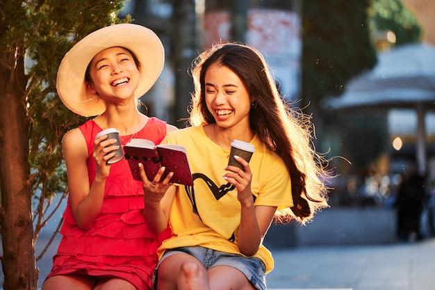 Twee aziatische meisjes met koffie en een blocnote die in een openluchtbank glimlachen