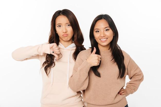 Twee aziatische mooie dameszusters die verschillende emoties tonen