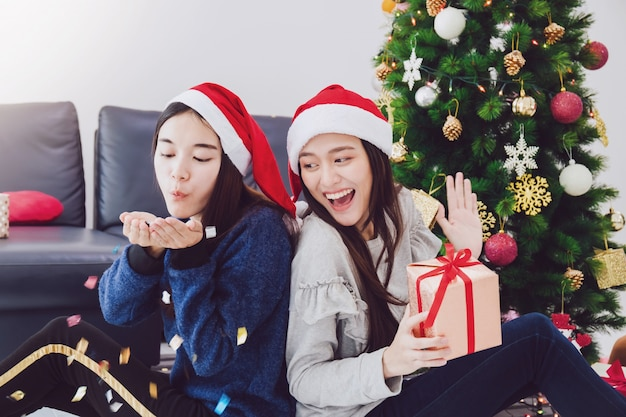 Twee aziatische mooie de giftdozen van de vrouwenholding. het glimlachen gezicht in ruimte met kerstboomdecoratie voor vakantie