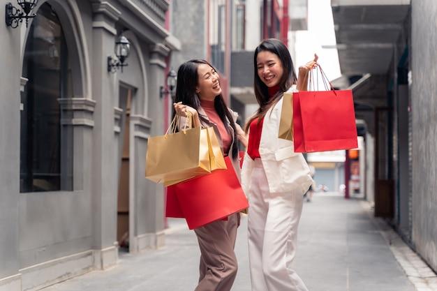 Twee aziatische mooie vrouwen met boodschappentassen in de stad over winkelcentrum achtergrond