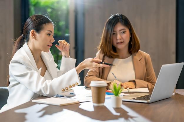 Twee aziatische onderneemsters die met de partnerzaken door puntpen aan technologielaptop werken