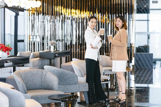 Twee aziatische onderneemsters die tijdens koffiepauze spreken in modern bureau