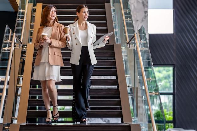 Twee aziatische ondernemers lopen en praten tijdens koffiepauze in moderne kantoor of coworking ruimte, koffiepauze, ontspannen en praten na werktijd, zakelijke en mensen partnerschap concept