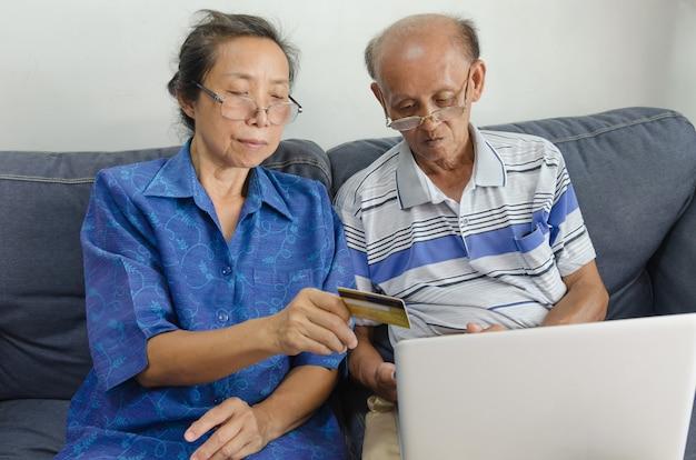 Twee aziatische ouderen online winkelen. senior bedrijf creditcard zittend op een bank met laptop thuis.