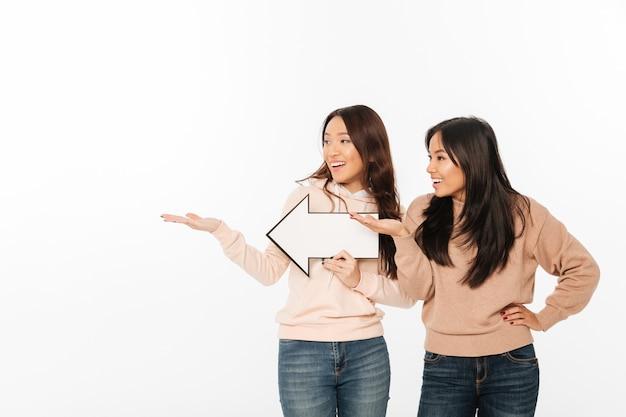 Twee aziatische positieve dameszusters die pijl houden die copyspace tonen.
