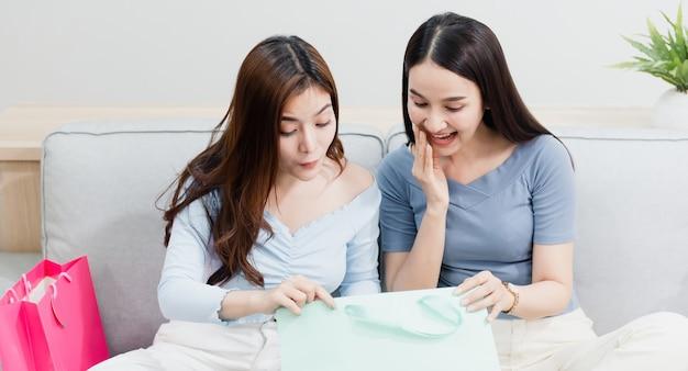 Twee aziatische schoonheidsmensen die de papieren zak openen met een blij lachend gezicht, als een nieuw normaal online bedrijf in de winkelervaring vanuit huis