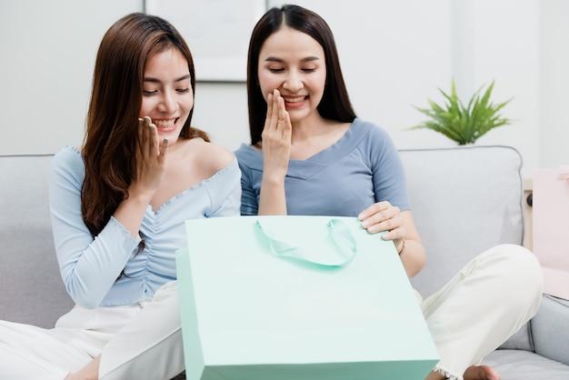 Twee aziatische schoonheidsmensen die de papieren zak openen met een blij lachend gezicht. nieuw normaal online zakendoen in de winkelervaring vanuit huis
