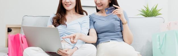 Twee aziatische schoonheidsmensen gebruiken een creditcard om via internet aankopen te doen met een laptop. met een blij lachend gezicht, een nieuw normaal online bedrijf zijn in de winkelervaring vanuit huis