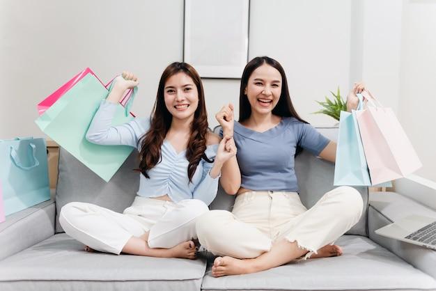 Twee aziatische schoonheidsmensen heffen hun papieren zakken op met een blij lachend gezicht, als een nieuw normaal online bedrijf in de winkelervaring vanuit huis