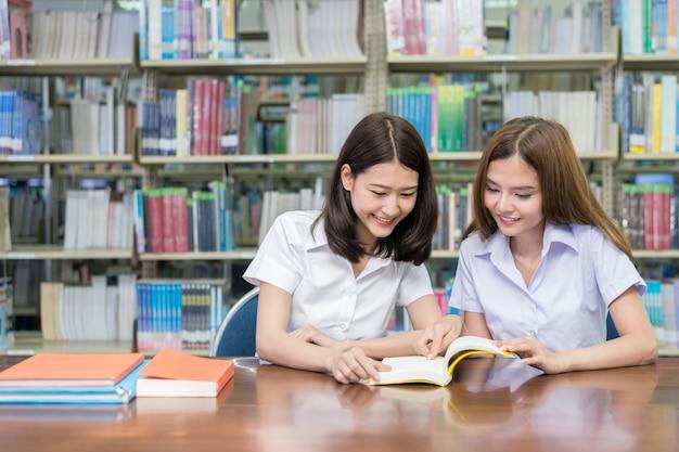 Twee aziatische studenten die samen in bibliotheek bij universiteit bestuderen.