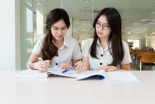 Twee aziatische studenten die samen studeren aan de universiteit.