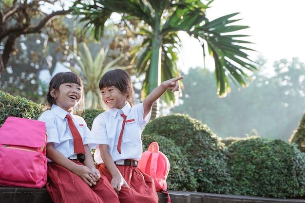 Twee aziatische studenten in uniform wijzen weg terwijl ze samen zitten