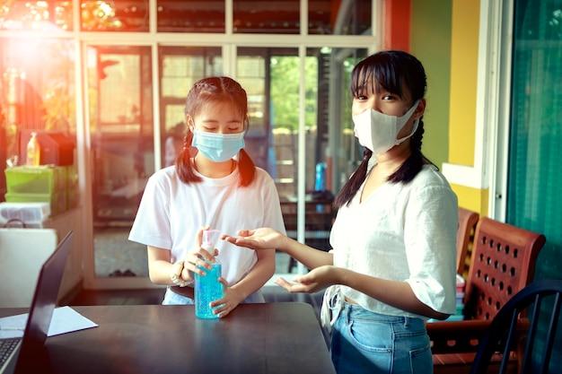 Twee aziatische tieners die een gezichtsmasker dragen dat de hand wast met alcoholgel