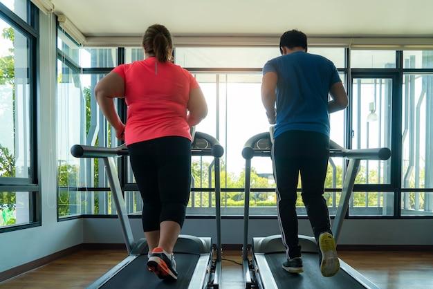 Twee aziatische trainer man en overgewicht vrouw trainen op de loopband in de sportschool