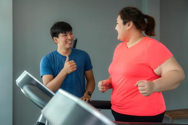 Twee aziatische trainerman en te zware vrouw die opleiding op tredmolen in gymnastiek uitoefenen.