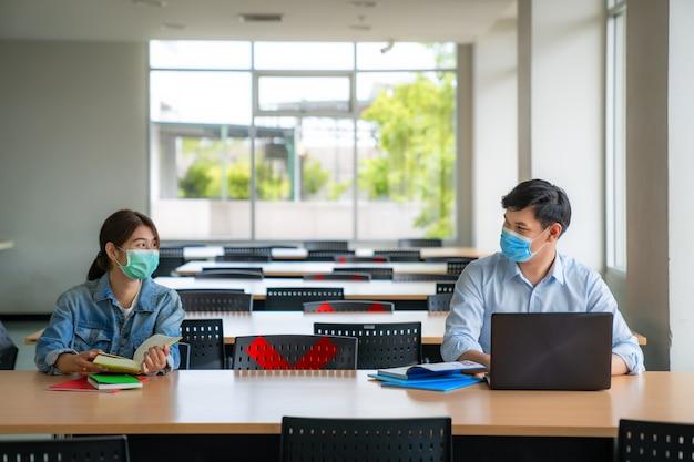 Twee aziatische universitaire studenten die gezichtsmasker dragen en in bibliotheek sociale afstand van andere zitten