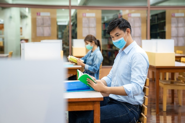 Twee aziatische universitaire studenten die gezichtsmasker in bibliotheek dragen