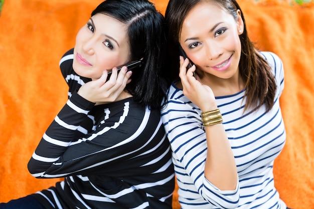 Twee aziatische vriendinnen met telefoon