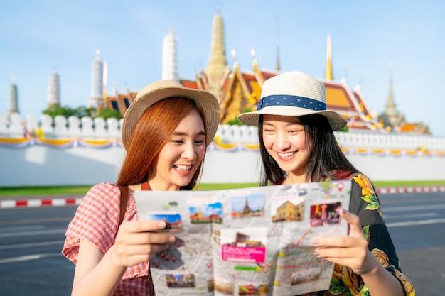 Twee aziatische vriendinnen reizen en controleren de locatie met een kaart