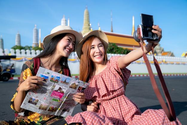 Twee aziatische vriendinnen reizen en nemen foto selfie in grand palace