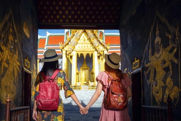 Twee aziatische vriendinnen reizen en passeren de toegangspoort naar grand palace