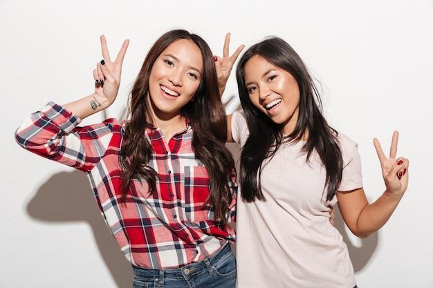 Twee aziatische vrij vrolijke dameszusters die vredesgebaar tonen.