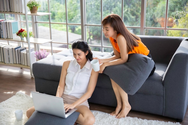 Twee aziatische vrouwelijke collega's die samen zitten en laptop kijken
