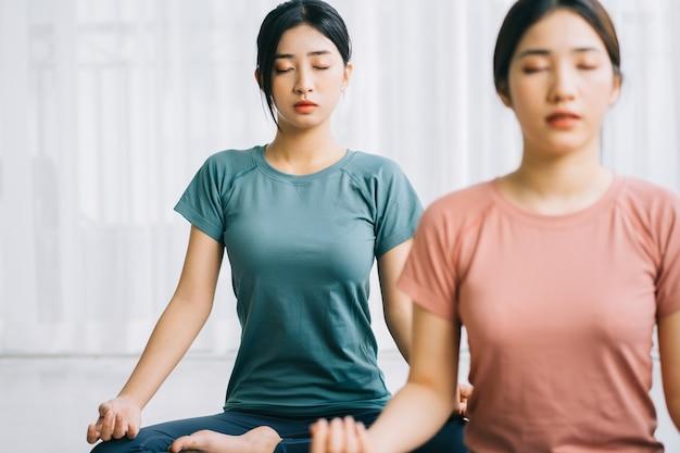 Twee aziatische vrouwen beoefenen thuis meditatie
