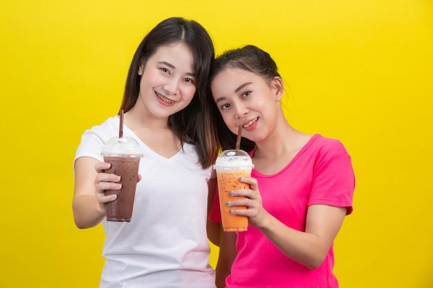 Twee aziatische vrouwen die bevroren melkthee en bevroren cacao op een geel drinken.