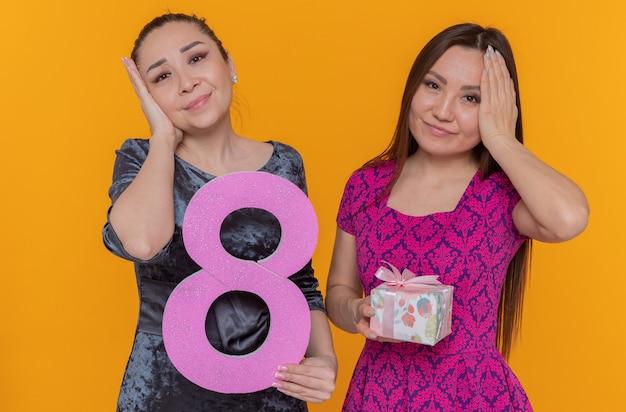 Twee aziatische vrouwen die de dag van de internationale vrouw vieren met nummer acht en aanwezig kijken naar de voorkant verward hand in hand op hoofden die zich over oranje muur bevinden