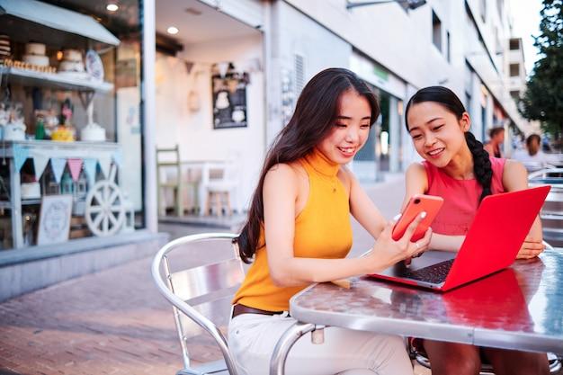 Twee aziatische vrouwen die een computer met behulp van openlucht